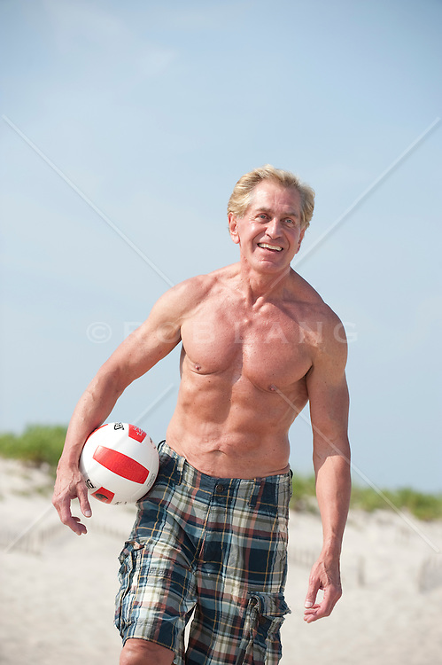 Shirtless mature man at the beach with a volleyball