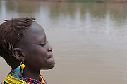 Young Dasanech girl blowing water out of her lips, Omovalley, Ethiopia,Africa