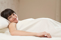 Portrait of smiling young pregnant woman lying on bed