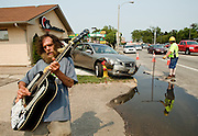 """Street performer Johnny """"Johnny Jam"""" Matthews plays guitar on Highway 30 near Eddy Street where a car collided with the A+ Real Estate Pros building and then a fire hydrant around 3:30 p.m. """"Too dangerous to jam here anymore,"""" said Mathews who frequently performs in that area. According to police Ahmed Fato was driving the 2005 Nissan Altima and was startled by something behind him causing him to accelerate while leaving the parking lot West of the realty business. Police estimated $500 of damage to the building, $4,000 to the car and over $500 to the fire hydrant which appeared to have been damaged below street level as well. (Independent/Matt Dixon)"""