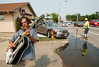 "Street performer Johnny ""Johnny Jam"" Matthews plays guitar on Highway 30 near Eddy Street where a car collided with the A+ Real Estate Pros building and then a fire hydrant around 3:30 p.m. ""Too dangerous to jam here anymore,"" said Mathews who frequently performs in that area. According to police Ahmed Fato was driving the 2005 Nissan Altima and was startled by something behind him causing him to accelerate while leaving the parking lot West of the realty business. Police estimated $500 of damage to the building, $4,000 to the car and over $500 to the fire hydrant which appeared to have been damaged below street level as well. (Independent/Matt Dixon)"