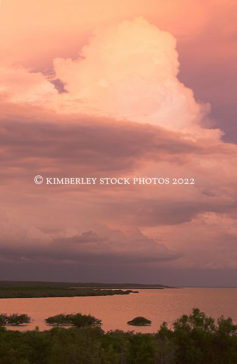 Beautiful pink wet season storm clouds reflect in the waters of Broome's Dampier Creek in Roebuck Bay.