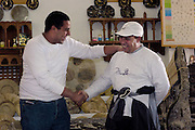 Two Moroccan men friends joking together, having met again after an absence.  Both are laughing.