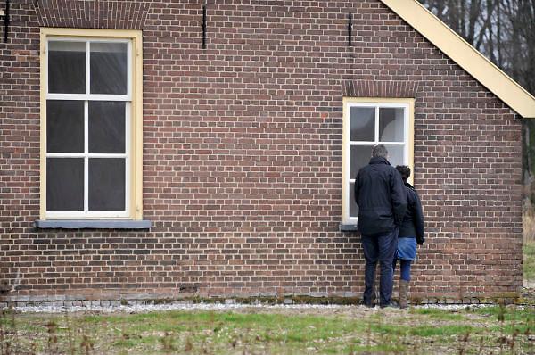 Nederland, Wijchen, 4-3-2012een echtpaar,stel, kijkt door het raam van een huis dat leeg staat. Het is een verbouwde boerderijn die te koop staat.Foto: Flip Franssen/Hollandse Hoogte