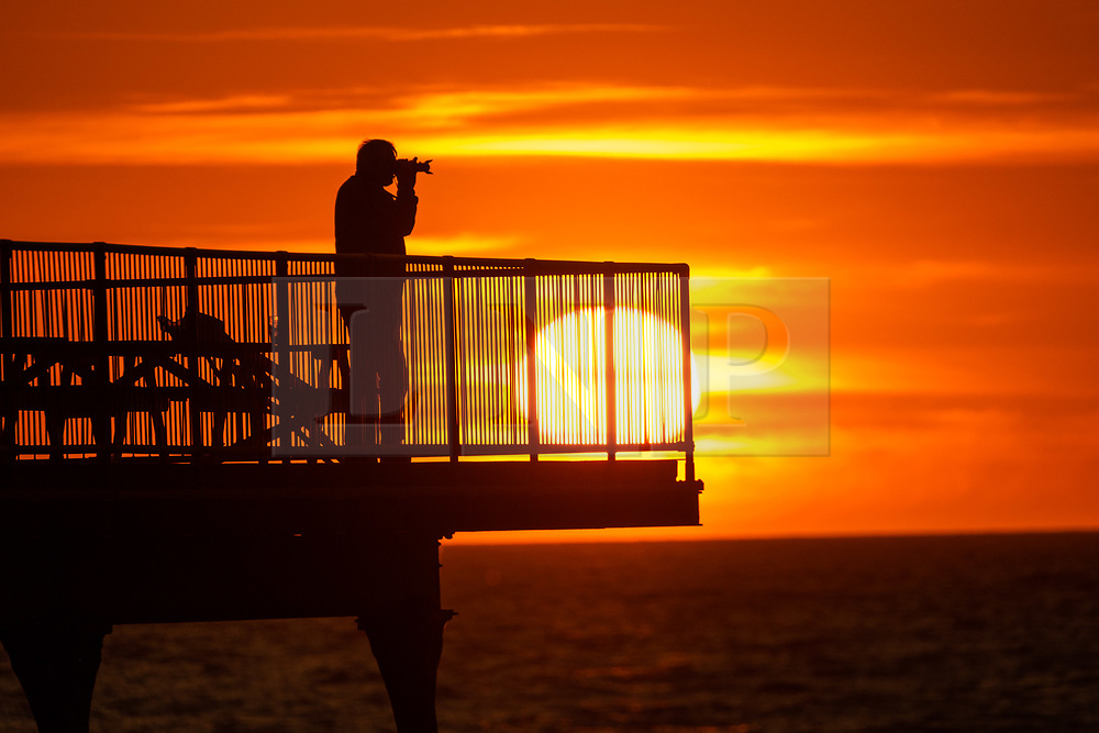 ©Licensed to London News Pictures.<br /> 03/07/2019. Aberystwyth, UK. People standing at the end of Aberystwyth's truncated seaside pier are silhouetted against the sky as they watch the glorious sunset  over  Cardigan Bay on the coast of west Wales. Photo credit: Keith Morris/LNP