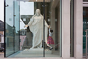 A devoted young girl hangs from the hand of a Jesus statue in the foyer of The Church of Jesus Christ of Latter-day Saints (Mormons) in central London, England.