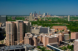 Aerial view of Texas Medical Center with foreground featuring MD Anderson Cancer Center Campus and downtown Houston skyline in the distance.
