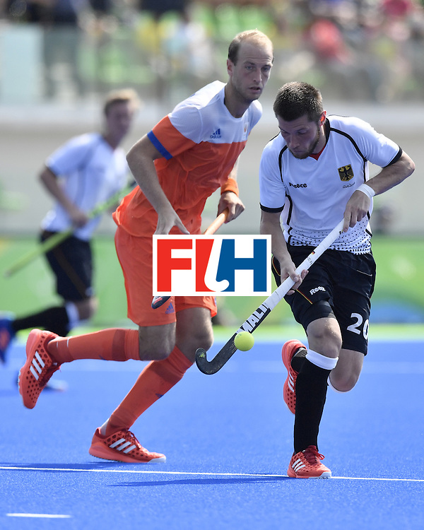 Germany's Martin Zwicker (R) vies with Netherlands' Billy Bakker during the men's Bronze medal field hockey Netherlands vs Germany match of the Rio 2016 Olympics Games at the Olympic Hockey Centre in Rio de Janeiro on August 18, 2016. / AFP / PHILIPPE LOPEZ        (Photo credit should read PHILIPPE LOPEZ/AFP/Getty Images)