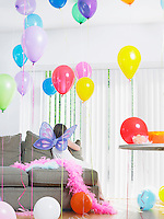Young girl (7-9) sitting on sofa with balloons wearing fairy wings back view