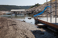 Slide on and abandoned boat dock that now ends in mud instead of water at a dried up branch of Lake Travis in Austin Texas.The Drought in Texas will have long term environmental and finical impact.