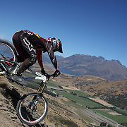 Matthew Walker from Kawerau in action during the NZBNZ South Island Downhill Cup mountain bike downhill series held on The Remarkables face with a stunning backdrop of the Wakatipu Basin. 150 riders took part in the two day event.  Queenstown, Otago, New Zealand. 9th January 2012. Photo Tim Clayton