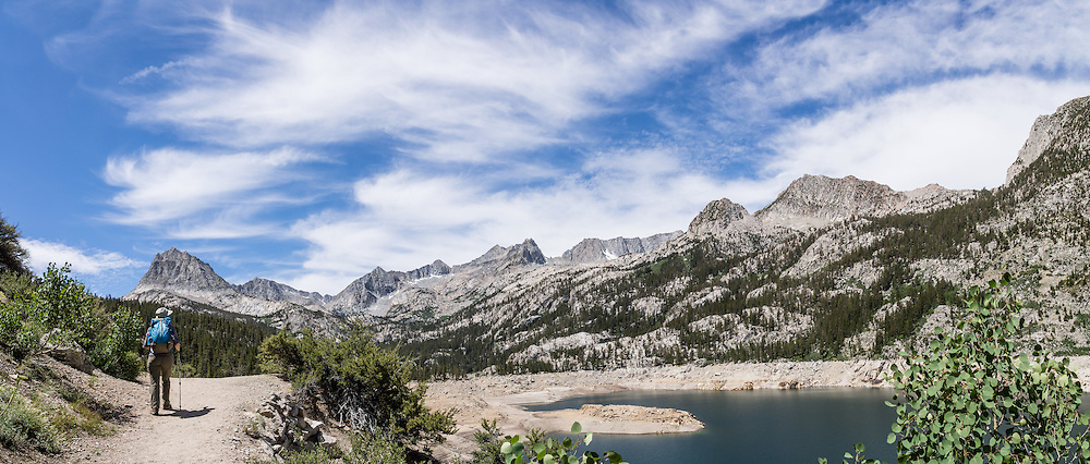 Hurd Peak (12,237 feet, left) rises above a hiker at the reservoir of South Lake in Inyo National Forest, Sierra Nevada, California, USA. My favorite hike in the Bishop Creek watershed goes from South Lake to Long Lake and Saddlerock Lake, looping back via a steeper, poorly marked route to Ruwau Lake, Chocolate Lakes, and Bull Lake, in John Muir Wilderness, Inyo National Forest, Sierra Nevada, California, USA. The rewarding semi-loop is 9 miles with 2220 feet cumulative gain. An easier walk is 7.2 miles round trip with 1500 feet gain to Saddlerock Lake, out and back via beautiful Long Lake.  This panorama was stitched from 3 overlapping photos.