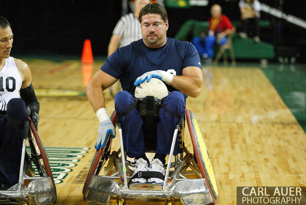 July 7th, 2006: Anchorage, AK - Scot Severn (9) moves the ball up the floor as William Groulx (10) moves in for a check as White defeated Blue in the gold medal game of Quad Rugby at the 26th National Veterans Wheelchair Games.