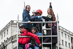 London, UK. 7 October, 2019. A specialist team of Metropolitan Police officers works to remove climate activists from Extinction Rebellion who had glued themselves to a scaffold tower to block Trafalgar Square on the first day of International Rebellion protests to demand a government declaration of a climate and ecological emergency, a commitment to halting biodiversity loss and net zero carbon emissions by 2025 and for the government to create and be led by the decisions of a Citizens' Assembly on climate and ecological justice.