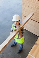 High angle view of female worker carrying wooden plank on shoulder