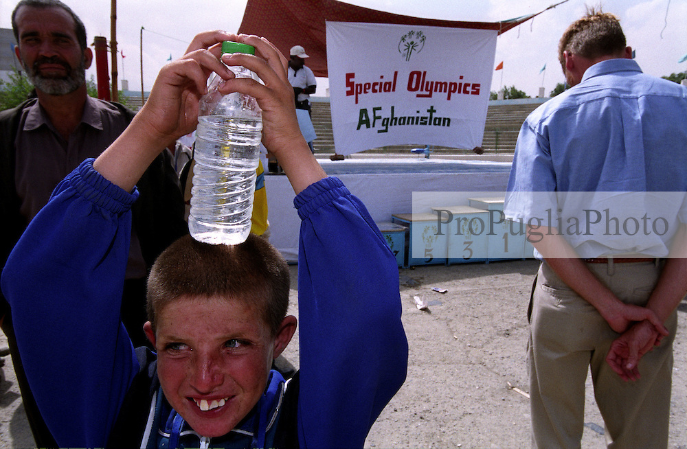 Kabul, 24 August 2005...Gazhi Stadium. A young Afghan athlete proubly hold his bottle of mineral water. Food, drinks, clothes and shoes was distributed  by SOA Staff to athletes and participants.....On 23-25 August 2005, Special Olympics Afghanistan held its first national Games at Olympic Stadium in Kabul. More than 300 athletes, including 80 female athletes, experienced a taste of happiness and achievement for the first time in their lives. They competed in athletics, bocce and football (soccer). Because of cultural restrictions, males and females competed at separate venues.