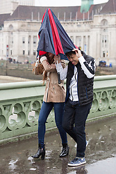 © Licensed to London News Pictures. 03/01/2016. London, UK. A couple try to shelter from heavy rain under a broken umbrella on Westminster Bridge in London.   London and the UK has experienced heavy rain and wind today. Photo credit : Vickie Flores/LNP