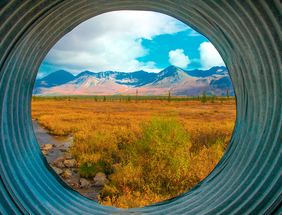 A pristine vantage point from inside a large culvert overlooking a stunning landscape in Alaska.