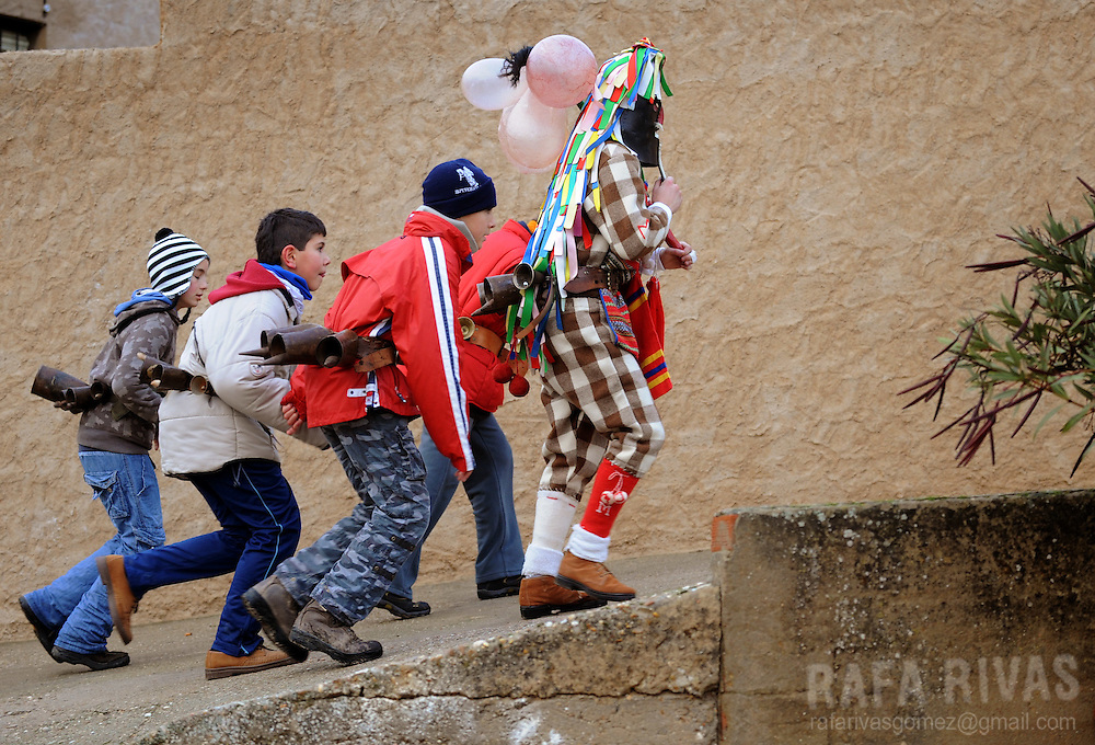 Zangarron (L) is followed by children as he visits the houses of the north western Spanish village of Sanzoles del Vino, Zamora province, to ask for the Christmas box, during this year's San Esteban festivities, on December 26, 2009. The pagan festival of Zangarron opens the winter mascarades' season in Zamora province, and it is celebrated to help the young men to become adults. Zangarron gives chase to people of the town as his mission is to protect the local eighteen years old boys from the people, so they can dance. Zangarron wears a black leather mask, colourful clothes, a whip and a stick with pig's bladders. Bladders represent fertility and the cowbells tied to his back frighten away the evil spirits.  PHOTO/RAFA RIVAS