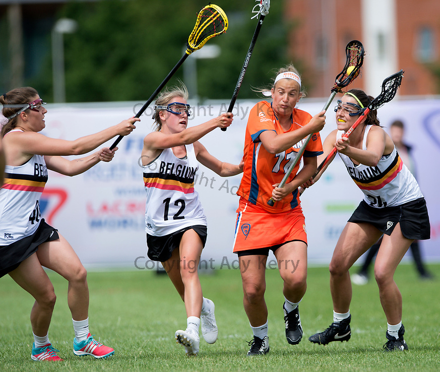 Belgium's , Sophia Klaber and Pascale D'Huyvetter  challenges with Netherlands' Kimberley Vuurboom at the 2017 FIL Rathbones Women's Lacrosse World Cup, at Surrey Sports Park, Guildford, Surrey, UK, 14th July 2017.