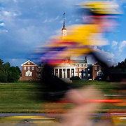 A cyclist wearing yellow and purple streaks past the Colby College quad and chapel.  The 2007 Trek Across Maine, an annual project of the American Lung Association of Maine (ALAM).