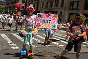 "New York, NY - 25 June 2017. New York City Heritage of Pride March filled Fifth Avenue for hours with groups from the LGBT community and it's supporters. A marcher from Gays Against Guns with a sign reading ""Flowers not guns."""