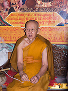 elderly Buddhist monk sits in the temple ready to receive visitors; close-up, Wat Phra That Doi Suthep; Ching Mai; Thailand