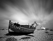 Clouds stream over an abandoned fishing boat on Dungeness beach. Pentax 67 with Ilford FP4