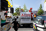 "A parade van with an ""AIDS is not over"" banner on it at Tokyo Rainbow Pride festival, Yoyogi Park, Tokyo, Japan. Sunday April 27th 2014 This was the third year this annual gay-pride event has been held in Japan capital.with food, fashion and health care stalls and musical performances set up in Yoyogi Park event square and a colourful parade around Shibuya at 1pm."