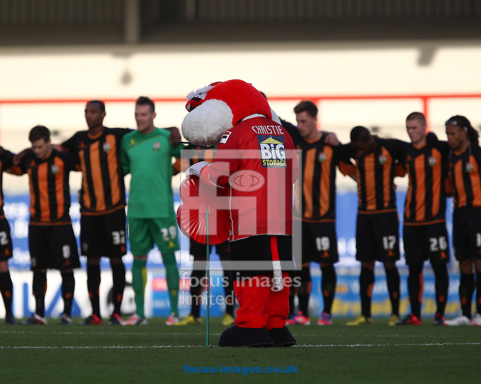 Picture by John  Rainford/Focus Images Ltd +44 7506 538356.10/11/2012.Morecambe mascot Christie the Cat stands with a giant poppy in front of the Barnet players before the npower League 2 match at the Globe Arena, Morecambe.