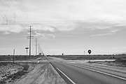 Black and white photo desert road landscape wall art. Quiet intersection on a country road. Antelope Valley, CA. Limited edition matted print. Fine art photography print.