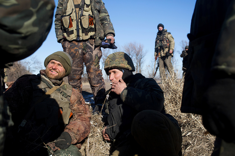 Soldiers smoke cigarettes and rest in a field on February 18, 2015 on a road about 35 kilometers from Debaltseve, Ukraine. The soldiers had withdrawn from Debaltseve earlier in the day and were regrouping at a crossroads before heading towards Artemivsk.