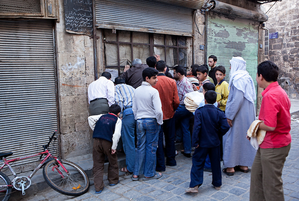 Early morning, people gather on the street outside the sales window of a bread factory, to get the daily staple of fresh flatbread, Aleppo, Syria