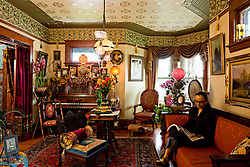 Step into Audry and Chris Bonds Southeast Portland home and travel back a century in time. An ornate grandfather clock chimes low tones in the entry, a fox fur stole is draped over a coatrack, and flickering gas lamps light the way into the living room. Both inside and out, the 1906 Queen Anne Victorians details are meticulously period, from the exterior paint color down to the copper cabinet hardware in the kitchen. We wanted to remain true to the style and era of the house, says Audry of the couples twenty-year adventure in decorating their home. It absolutely fits us and our lifestyle.