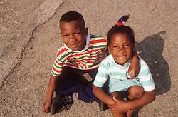 Young brother and sister sitting on ground outside,