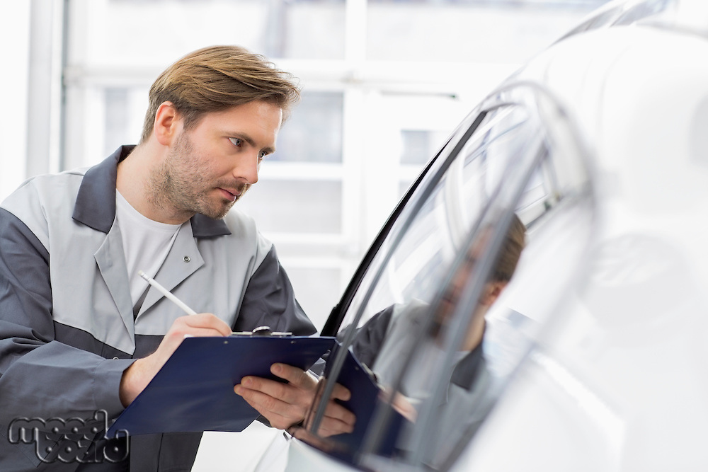 Mid adult repair worker writing on clipboard while examining car in workshop