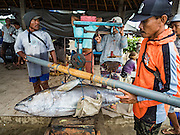 18 JULY 2016 - KUTA, BALI, INDONESIA:  Workers weigh yellowfin tuna at Pasar Ikan pantai Kedonganan, a fishing pier and market in Kuta, Bali. The fish were caught by trawlers working in Indonesian waters and transferred to smaller boats which then brought the yellowfin into shore. Yellowfin are extremely popular with Japanese consumers for sushi and sashimi and the best yellowfin caught in Indonesian waters are sent directly to Japan.   PHOTO BY JACK KURTZ