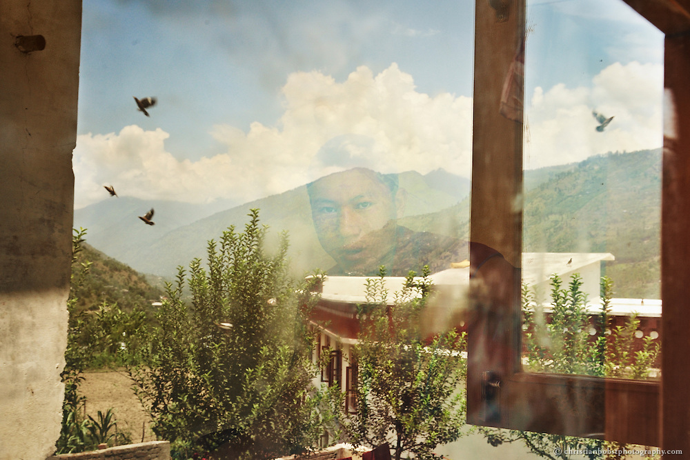 A tibetan monk looks through the window of his room at the Dagpo Sherdrub Ling Monestary in India, while we see the reflection of the mountains of the Kullu Valley and some parts of the monastery in the window.