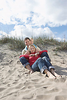 Parents and daughter (5-6) embracing on beach portrait
