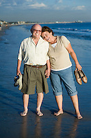 Senior couple standing on beach, portrait