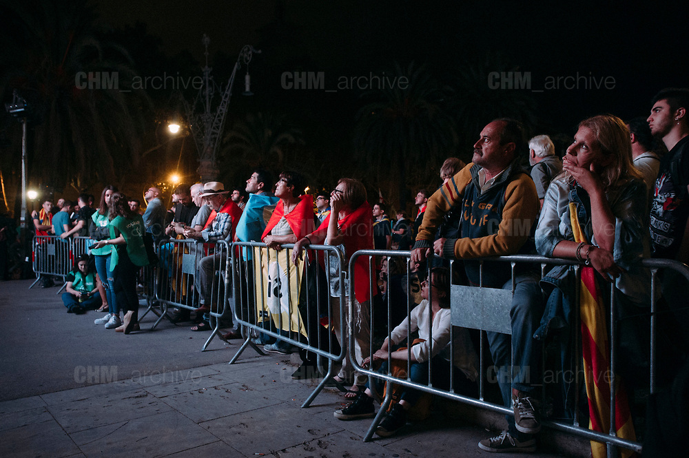 """Supporters of an independence for Catalonia  listen to Catalan president Carles Puigdemont's speech broadcasted on a television screen at the Arc de Triomf (Triumphal Arch) in Barcelona on October 10, 2017. Catalonia's leader Carles Puigdemont said Tuesday he accepted the """"mandate of the people"""" for the region to become """"an independent republic,"""" but proposed suspending its immediate implementation to allow for dialogue.  10, 2017 in Barcelona, Spain. Christian Mantuano / OneShot"""