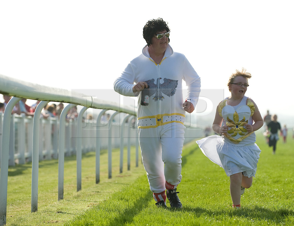 © Licensed to London News Pictures. 25/03/2012..Redcar racecourse, Redcar, cleveland..Elvis aka Peter Reidy and his daughter Charlotte from Brotton in Cleveland take part in the sports relief mile at Redcar racecourse...Hundreds of people took part in the charity sports relief mile at the racecourse at Redcar in Cleveland to help raise money for the charity event. Participants had the choice of running either one, three or six miles...Photo credit : Ian Forsyth/LNP