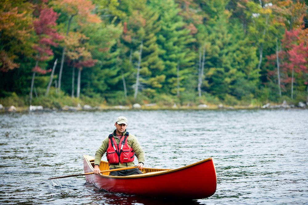 A man paddles his canoe on Seboeis Lake near Millinocket, Maine.  Fall. (MR)