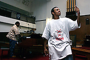 Donovan, 17, a member of the Hells Most Wanted, a Christian Hip Hop group, is dancing, Rev. Ferguson, of the Music Ministry, and co-founder of the Hip Hop Church NY, is playing music from the background,  during a Mass Service at the Hip Hop Church in Harlem, New York, NY., on Thursday, June 22, 2006. A new growing phenomenon in the United States, and in particular in its most multiethnic city, New York, the Hip Hop Church is the meeting point between Hip Hop and Christianity, a place where ëGodí is worshipped not according to religious dogmatisms and rules, but where the ëHoly Spirití is celebrated by the community through young, unique, passionate Hip Hop lyrics. Its mission is to present the Christian Gospel in a setting that appeals to both, those individuals who are confessed Christians, as well as those who are not regularly attending traditional Services, while helping many youngsters from underprivileged neighbourhoods to feel part of a community, to make them feel loved and to help them not to give up when problems arise. The Hip Hop Church is not only forward-thinking but it also has an important impact where life at times can be difficult and deceiving, and where young people can be easily influenced for the worst purposes. At the Hip Hop Church, members are encouraged to sing, dance and express themselves in any way that the ëSpirit of Godí moves them. Honours to students who have overcome adversity, community leaders, church leaders and some of the unsung pioneers of Hip Hop are common at this Church. Here, Hip Hop is the culture, while Jesus is the centre. Services are being mainly in Harlem, where many African Americans live; although the Hip Hop Church is not exclusive and people from any ethnic group are happily accepted and involved with as much enthusiasm. Rev. Ferguson, one of its pioneer founders, has developed ëHip-Hop Homileticsí, a preaching and worship technique designed to reach the children in their language and highlight their sensibiliti