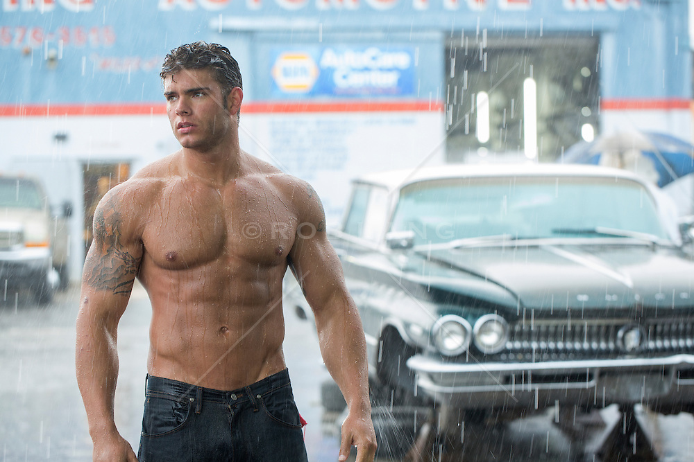 shirtless auto mechanic at a garage shirtless muscular auto mechanic with dirt on his face and  body at an auto body repair shop