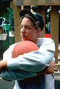 17 year old high school student thoughtfully hugging basketball.  St Paul Minnesota USA