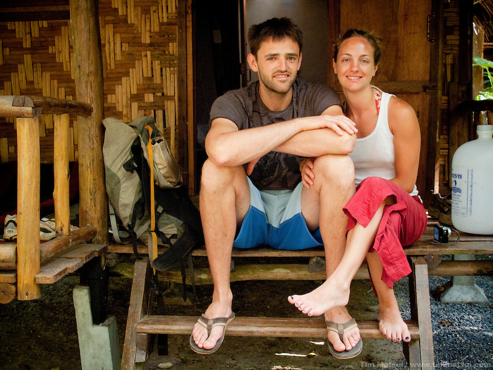 A young caucasian couple on the steps of a bungalow in Tonsai, Thailand.