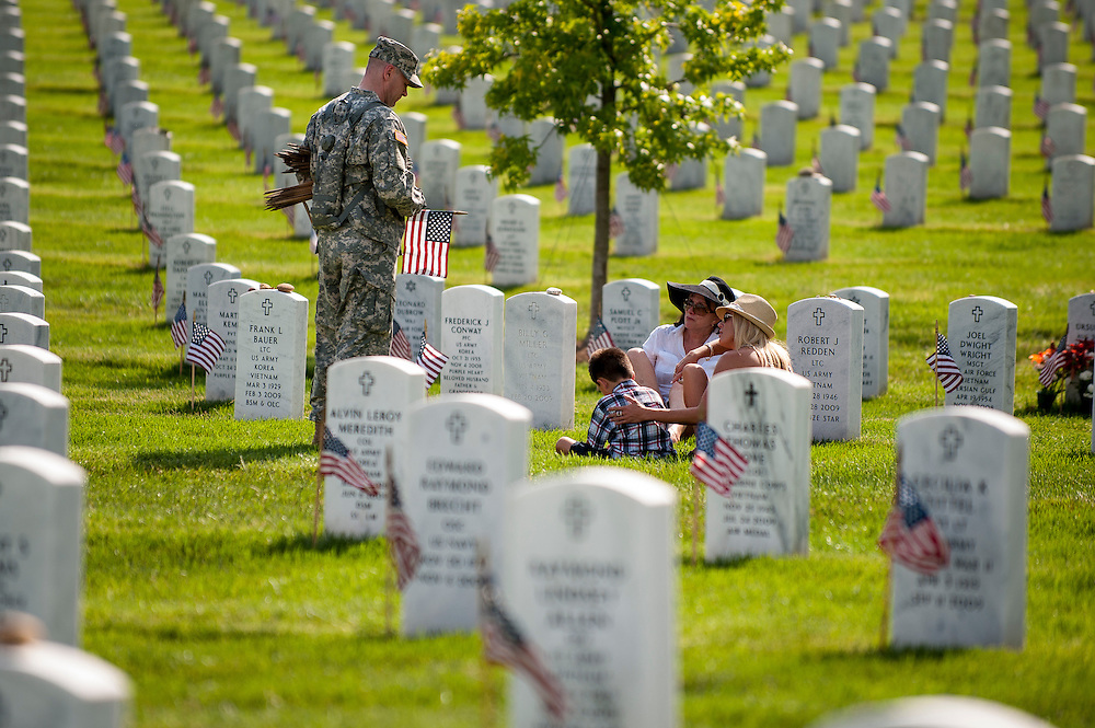 "A member of the 3rd U.S. Infantry, known as The Old Guard, speaks with a family as he places American flags before gravestones and niches of service members buried at Arlington National Cemetery in advance of the Memorial Day weekend. The tradition, known as ""flags in,"" is conducted annually since 1948. Every available soldier in the 3rd U.S. Infantry participates, placing small American flags one foot in front and centered before more than 260,000 gravestones and about 7,300 niches at the cemetery's columbarium. Old Guard soldiers remain in the cemetery throughout the weekend, ensuring that a flag remains at each gravestone."