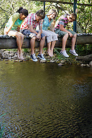 Four teenagers (16-17 years) sitting on wooden bridge looking down at stream smiling