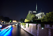 Long exposure night photo of Notre Dame cathedral and the Seine River with the blur of a passing tour boat.